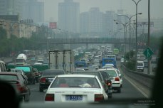 Congested traffic with smog haze obscuring buildings in the distance
