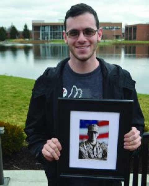 Freshman Keegan D'Alfonso, 25, holds a photo of himself in uniform. D'Alfonso served as a sergeant in the Marine Corps for five years before enrolling as a journalism major at Cedarville (photo: Rebecca Carrell).
