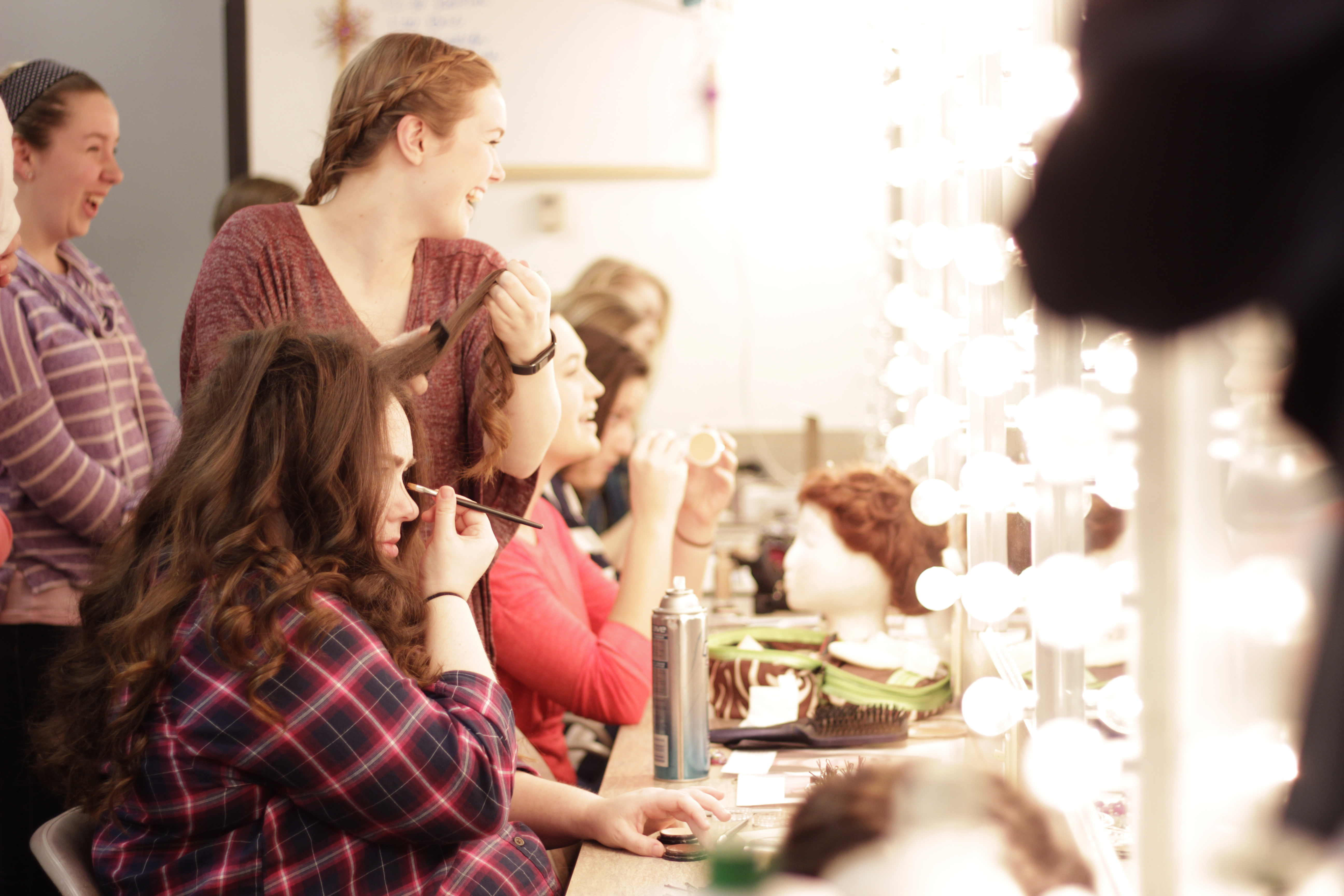 Sophomore and hair/makeup crew head Paige Baker helps senior Kaleigh Kenney with her hair as actors prepare for one of the last nights of dress rehearsals. Kenney played Mrs. Squires, one of the Pick-A-Little ladies, while Baker played one of the dancing teens.