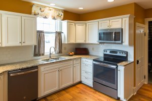 After: The kitchen is now light, spacious, and the fridge is neatly tucked away, yet still accessible and in reach.