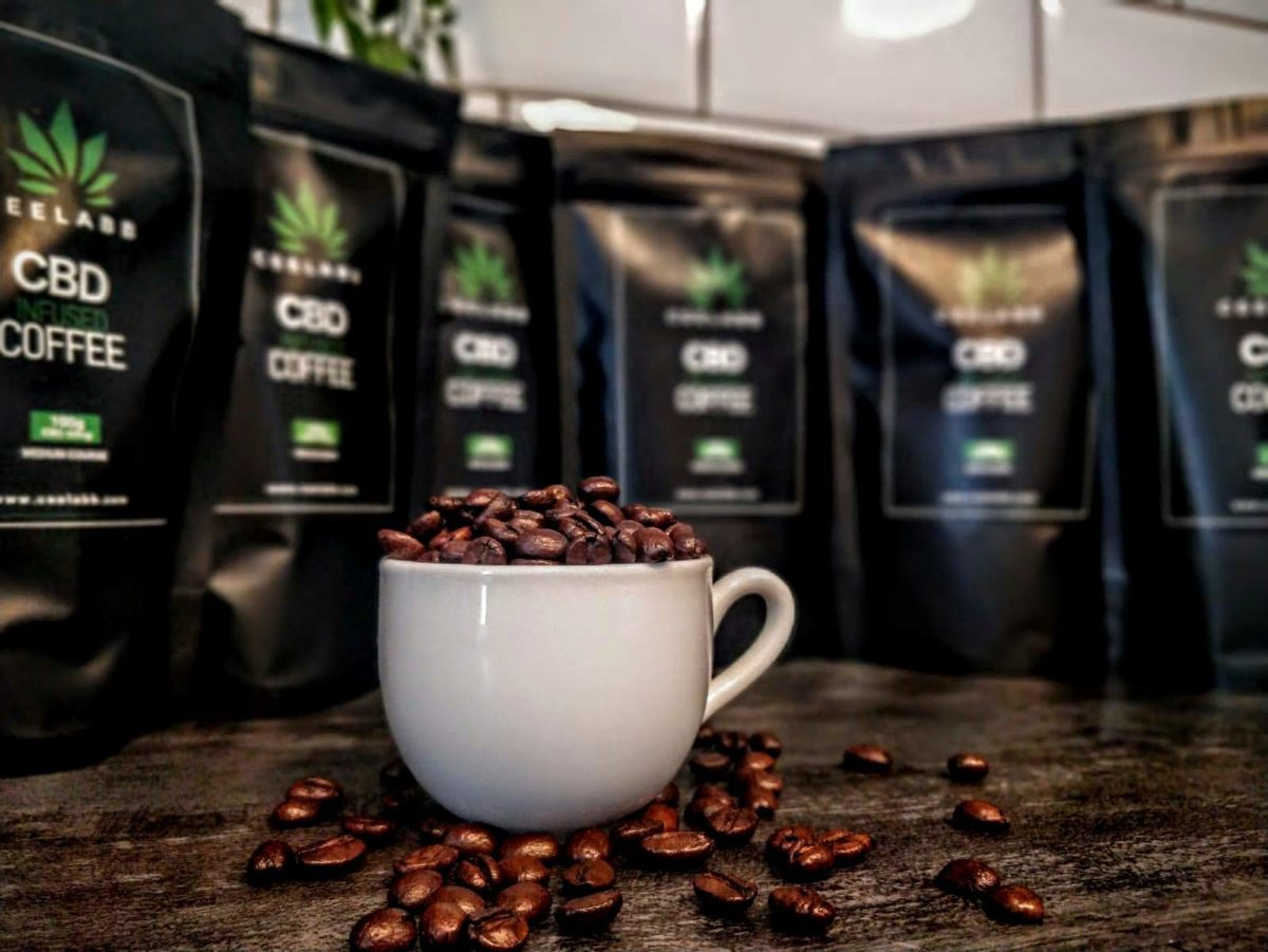 Ceelabb CBD infused Coffee beans in an espresso cup with Ceelabb 100gram bags of cbd coffee in background