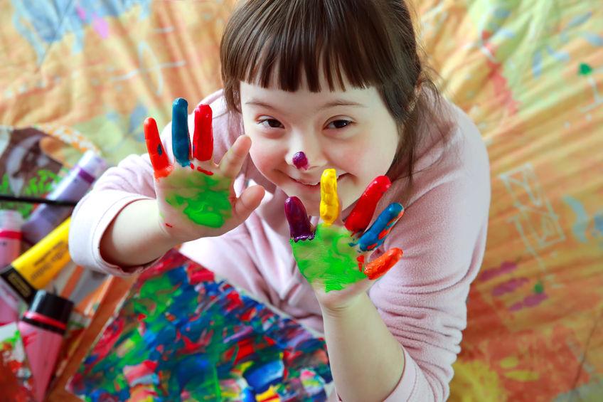 Niña con Síndrome de Down con las manos pintadas de colores