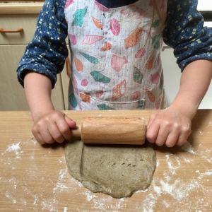 enfant qui étale une pâte au rouleau à pâtisserie