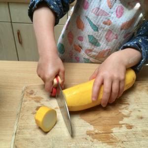 enfant qui coupe une courgette en tronçons