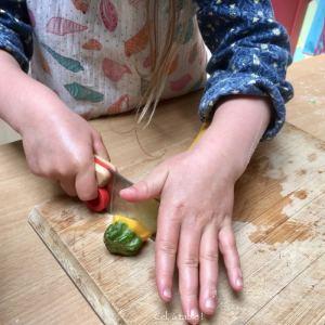 enfant qui coupe l'extrémité de la courgette