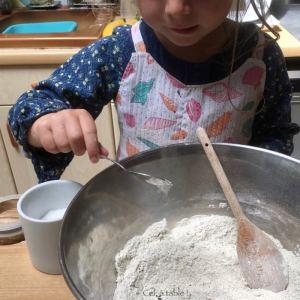 Enfant qui rajoute une pincée de sel dans le saladier