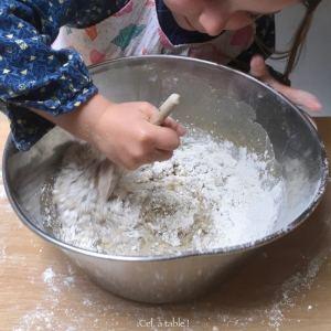 Enfant qui mélange une pâte à tarte avec une cuillère en bois
