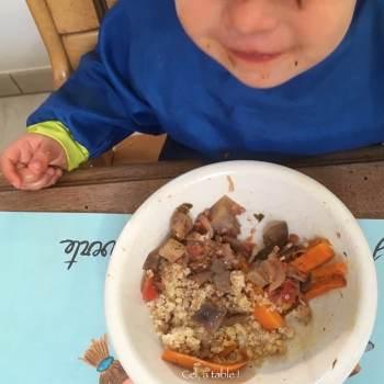 enfant qui mange une assiette de légumes et de céréales