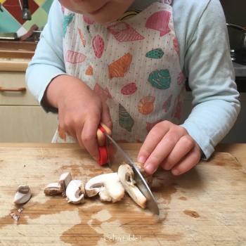 enfant qui coupe des champignons