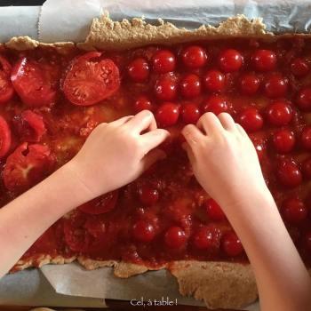 enfant qui dispose des tomates cerise pour pizza maison