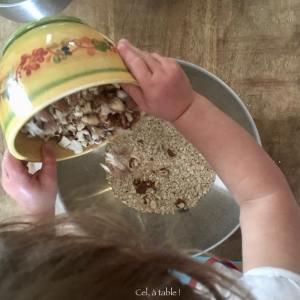 jeune enfant qui verse des amandes et noisettes concassées pour faire des céréales