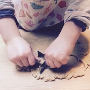 enfant qui découpe des formes à l'emporte-pièce