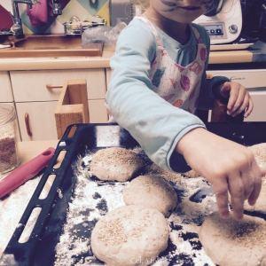 enfant qui saupoudre des pains de graines de sésame