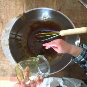 enfant qui rajoute de l'huile dans un saladier