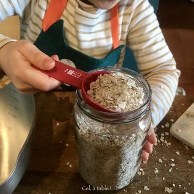 enfant qui remplis une tasse avec des flocons de sarrasin