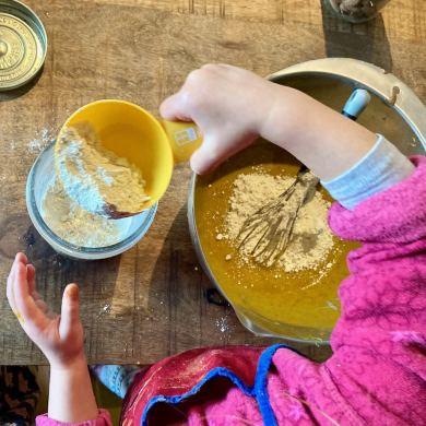 enfant qui rajoute de la farine