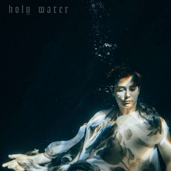 """CeCe submerged in water wearing a flowy white top with the words """"Holy Water"""" in the top left"""