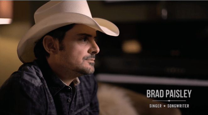 Still from It All Begins With A Song film of Brad Paisley sitting and leaning forward with a white cowboy hat on his head