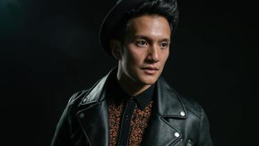 "Vincent Bueno from the ""Alive"" music video wearing a leather jacket, a black hat, and a netted see-through black shirt."