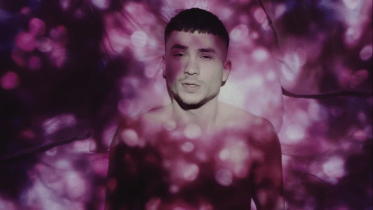 """Still from the """"Talking In My Sleep"""" music video which sees Paul Rey lying in a bed with white sheets, topless, as a projector displays pink spotted lights on him and the bed."""