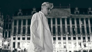"Loïc Nottet in the music video for ""Mr/Mme"" wearing a white oversized shirt looking off to the right located in Brussels."