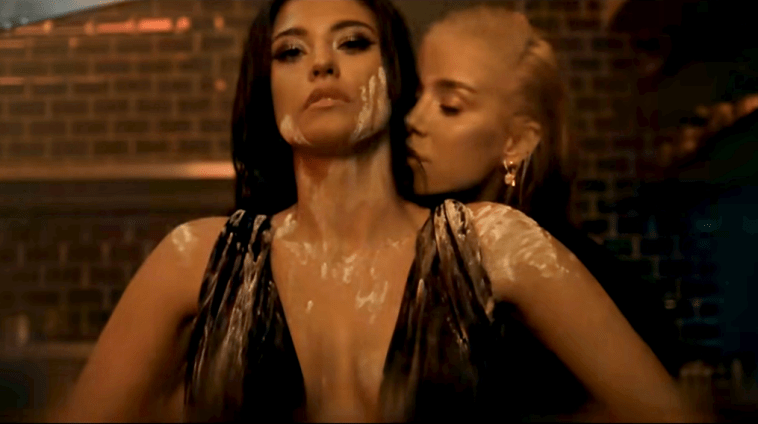 "Still from the ""Como Ay"" music video which sees Antonia caked in flour with Alina Ceusan behind her, brushing her face near Antonia's neck."