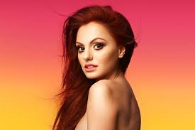 Alexandra Stan with auburn hair, looking at the camera over her shoulder.