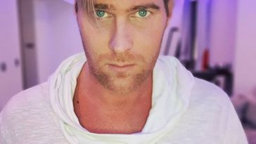 Basshunter taking a selfie wearing a white t-shirt with a bulky collar, and neon blue lights behind him.