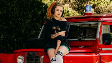 Janet Devlin promo shot for interview, she is on the bonnet of a red truck, wearing a black jumper and some headphones, and knee-high socks.