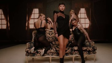 "Music video still from ""VKTM"" by SICKOTOY, INNA & TAG, which sees INNA standing infront of a sofa with four backing dancers, all dressed in black provocative clothes."