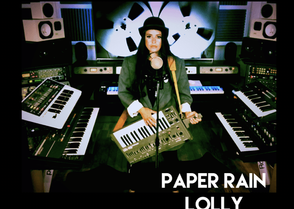 """The single cover artwork for """"Paper Rain"""" which sees Lolly in the studio with her keytar and keyboards around her as she sings into a mic."""