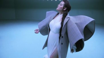 "Still from the ""Cuckoo"" music video which sees Netta in a white dress with an oversized jacket with wing-like sleeves and her hair over one shoulder."