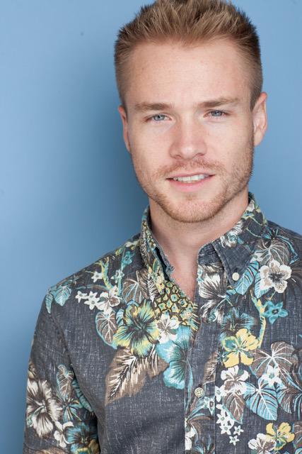 Press photo of Sam Clark wearing a flower-y shirt.