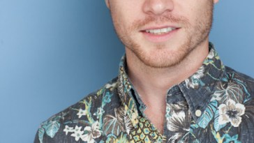 Press photo of Sam Clark wearing a flower-y shirt.