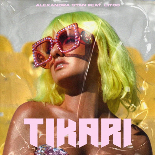 """Single artwork for """"Tikari"""" which sees Alexandra Stan wearing a lemon green wig cut into a shoulder-length bob paired with Gucci pink glasses with plastic yellow seats behind her."""