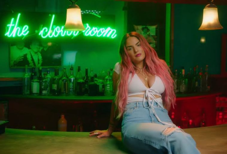 "Still from the ""What U Need"" music video which sees JoJo with pink hair, sitting on a bar top, wearing a white strap bra and high-waist jeans"