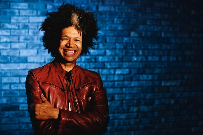 Press photo of Marc Lottering laughing at the camera with his arms crossed, donning a deep brown leather jacket.
