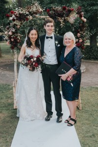wedding couple standing with wedidng celebrant after the ceremony