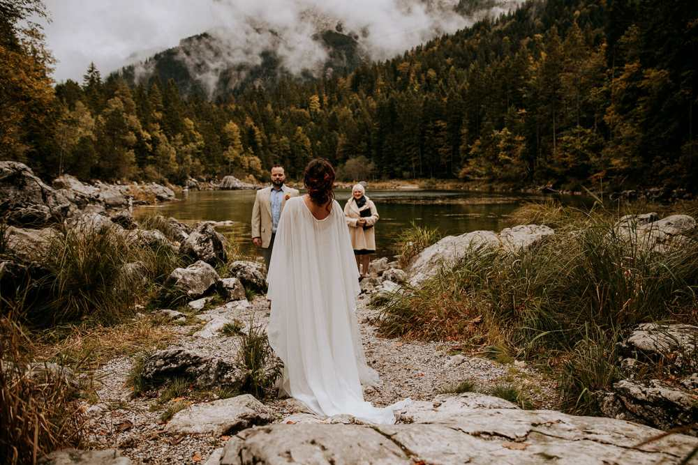 A mountain in Germany with a lake at which a couple are meeting to elope with a Celebrant leading their wedding ceremony. The bride is wearing a long white dress with a long cape which flows behind her.