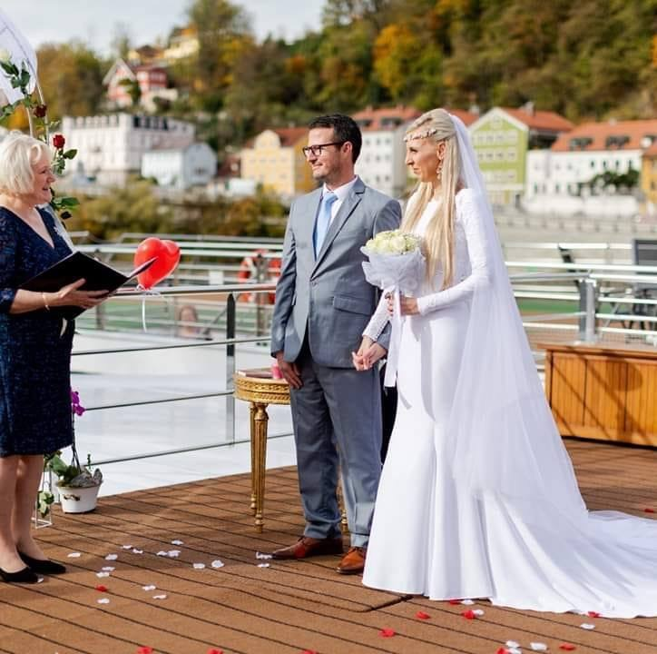 Man and Woman in wedding dress, with their wedding celebrant, on a river boat on the Danube in Germany