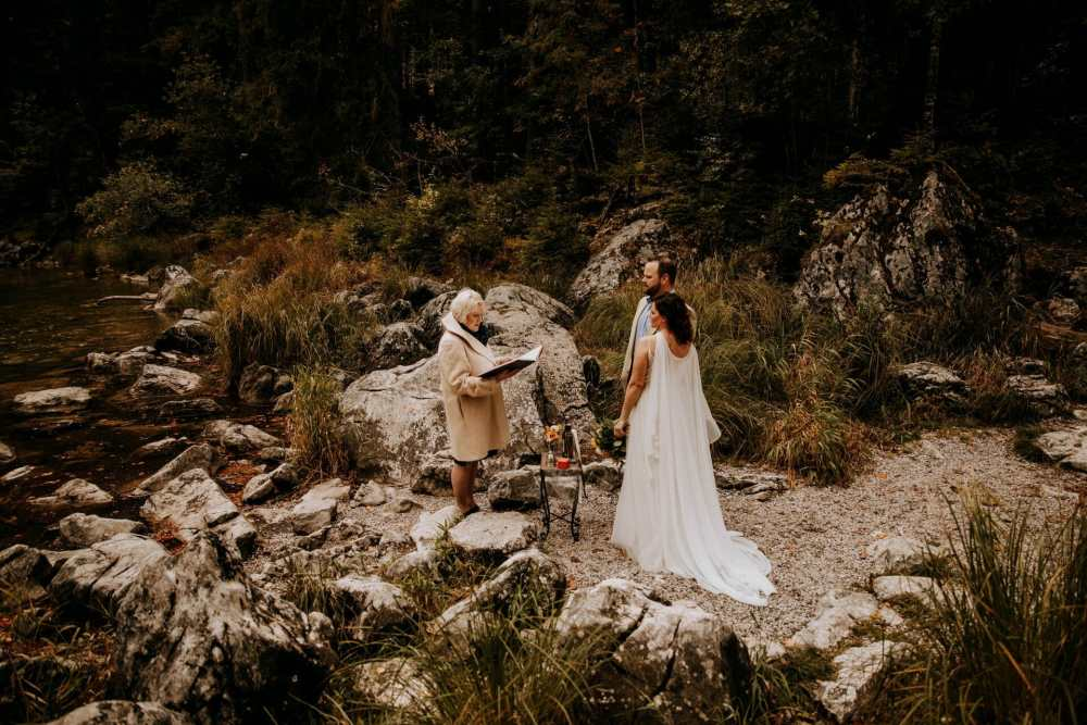 Man and woman in a wedding dress in an outdoor location by a lake, saying wedding vows with their wedding celebrant
