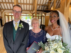 YVONNE STANDS BETWEEN A WEDDING COUPLE SHE HAS CREATED A WEDDING CEREMONY FOR. THE GROOM IS IN A GREY SUIT AND THE BRIDE IS SMILING AT THE CAMERA AND HOLDING HER CREAM ROSES BOUQUET