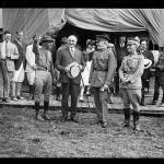 """Reenactment of Pickett's Charge at the battle of Gettysburg in Pennsylvania. Smedley Butler, President Warren Harding, John J. Pershing, and John Archer Lejeune in front of canvas """"White House"""""""