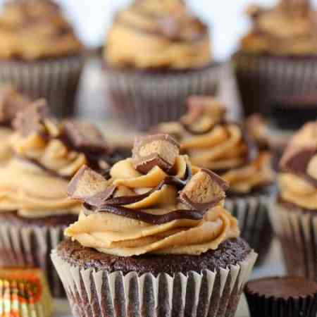 Chocolate Peanut Butter Cupcakes - Moist chocolate cupcakes stuffed with peanut butter cups and topped with peanut butter frosting and chopped peanut butter cups.