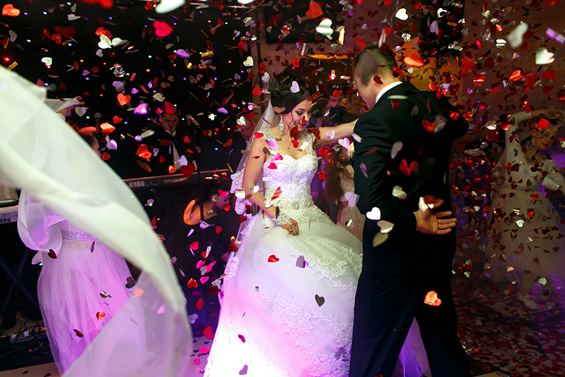 White and red heart-shaped confetti falls from above as a newly-married husband and wife dance.