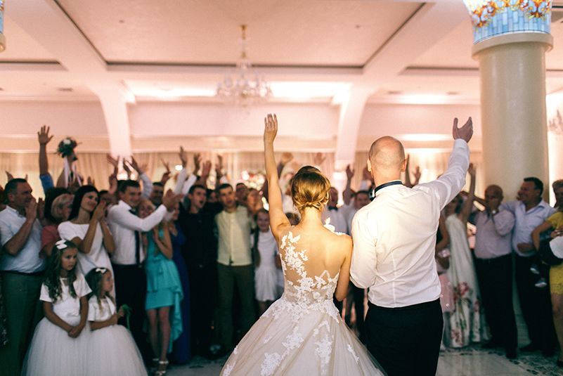 A bride and groom wave to all of their guests after completing the opening dance.