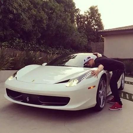 Rob Dyrdek hugging his white Ferrari 458 Italia.