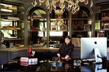 Kylie sitting in a businessman chair with her legs on the table and a bunch of stuff belonging to her mother in her home.