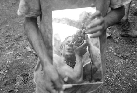 Photographer Moises Arias taking a Photography shot of himself in a mirror held by someone else, with his favorite camera..
