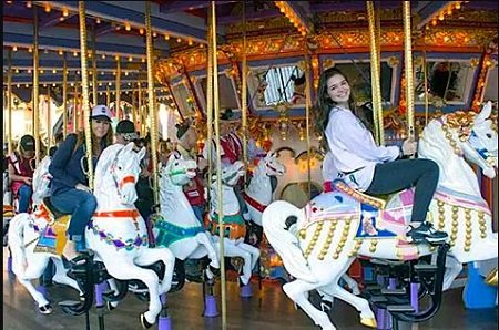"""Nicole Boice (left), Founder and CEO of Global Genes, and Madison McLaughlin, star of """"Arrow"""" taking a ride on the King Arthur Carousel during the """"Carousel of Possible Dreams"""" fundraiser for the Festival of Children Foundation at Disneyland in 2016. (Photo by Mark Eades, Orange County Register/SCNG)"""